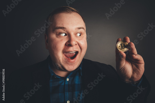 Photo Golden Bitcoin in fat funny man hand, Digitall symbol of anew virtual currency