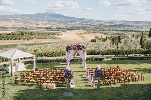 Leinwand Poster arch, decorated with trunks and flowers, stands in the wedding ceremony area on