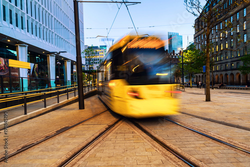 Light rail yellow tram in the city center of Manchester, UK in the evening