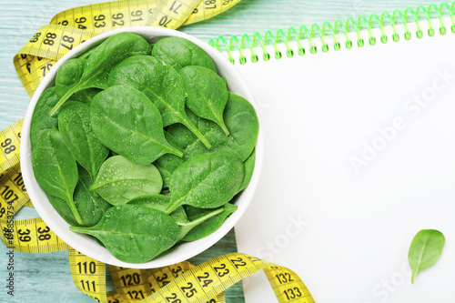 Clean notebook, green spinach leaves and tape measure on wooden table from above. Diet and healthy food concept.