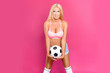 canvas print picture - Sexy blonde with attractive figure posing with a soccer ball on a pink background