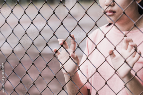 Fotografering  teen behind the cage or woman jailed, unhappy girl hand sad hopeless at fence prison in jail, no free and freedom struggle teen concept