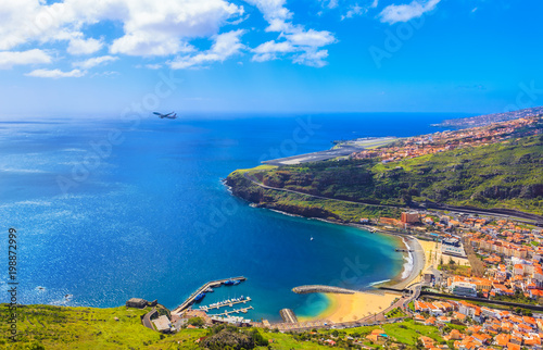 Spoed Foto op Canvas Eiland Aerial view of Machico bay in Madeira, with an airplane taking off against the ocean and the coastline of island in Portugal