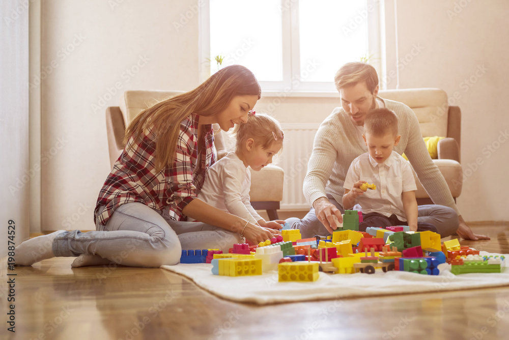 Fototapeta Parents with children having fun and playing together with toy blocks