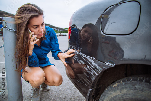 Fototapeta woman stand near scratched auto. call for help. car insurance obraz
