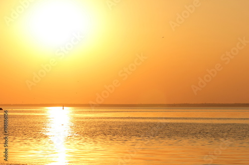 Poster Zee zonsondergang Orange sun over the sea horizon, beautiful sunset, copy space, landscape with a big sun, bloody horizon above the water surface, blank for the designer, orange pattern