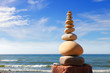 White, round stones balance on a background of blue sky and sea