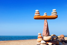 Symbolic Scales Of Stones On A Background Of Blue Sky And Sea.