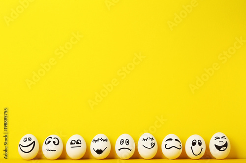 Eggs with funny faces on yellow background