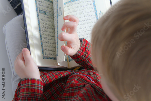 Little muslim European boy with islamic holy book Quran or Kuran
