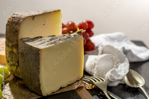 Foto op Aluminium Alpen Tasting of ancient french demi soft cheese Tomme from French Alps, made from cow, goat or sheep skim milk, low fat french cheese
