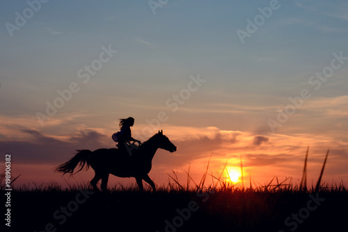 Fotografía  Romantic equine and girls silhouette on horse hiking with red rising sun on horizon