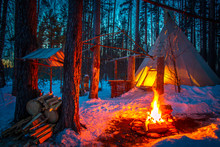 Tipi In The Snow-covered Forest. Indian Parking. The Bonfire Burns At The Entrance To The Wigwam. The Home Of The Indians Of Tipi. Wigwam In Winter.