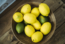 A Dish Of Lemons And Limes On The Wooden Table