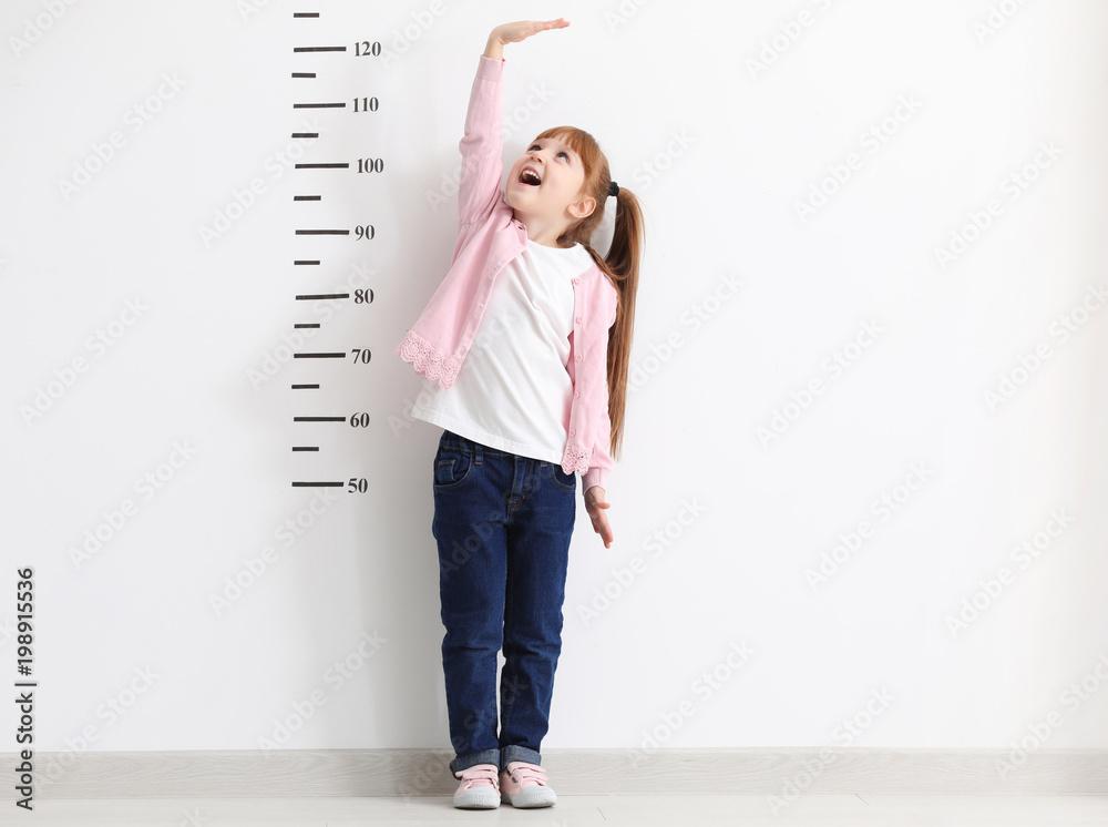 Fototapety, obrazy: Little girl measuring height near white wall