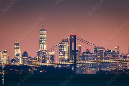 Photo  Manhattan skyline at dawn rises behind Verazzano Bridge