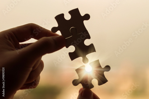 Obraz Silhouette Woman hands connecting couple puzzle piece against sunrise effect, businesswoman holding jigsaw with sunset background. Business solutions, target, success, goals and strategy concepts - fototapety do salonu