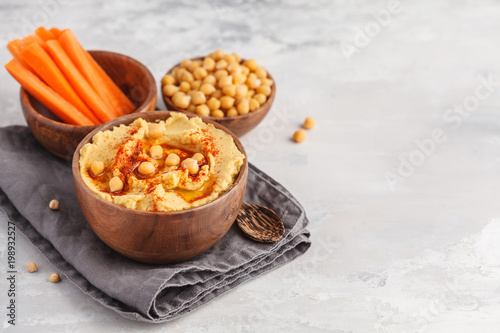Valokuva  Hummus, fresh carrot sticks and boiled chickpeas in wooden bowls