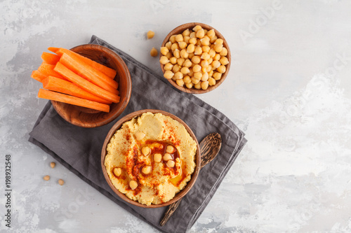Hummus, fresh carrot sticks and boiled chickpeas in wooden bowls. Vegan food concept, light background, copy space, top view