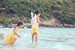 Two cute asian little child girls having fun to play and jump on beach together in summer vacation