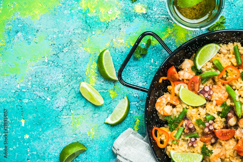 Seafood paella in pan served with beer and lime