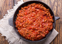 Pan Of Sauce Bolognese On Wooden Table