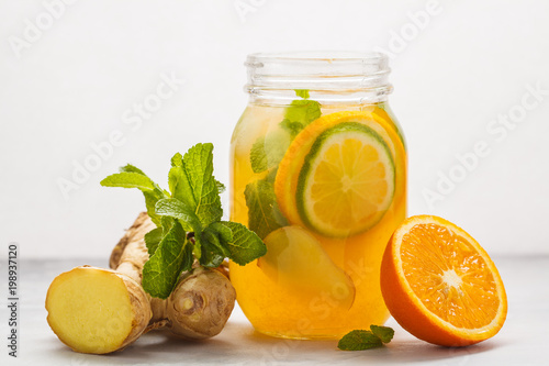 Ginger orange tea with mint in a glass jar, white background, copy space. Summer refreshing drink concept.