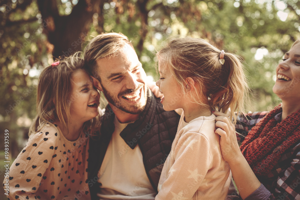 Fototapety, obrazy: Happy family in park having conversation and hugging.