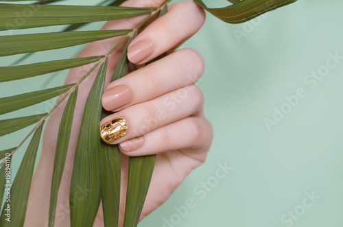 Beautiful female hand with beige nail design Fototapeta