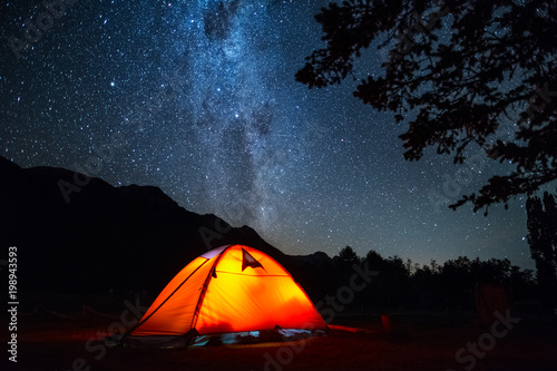 Poster Camping Tent and night sky. Highlighted orange hiking tent and deep starry sky with trees on the foreground.