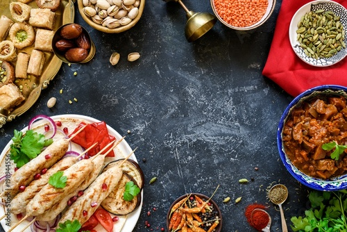 Turkish or arabic cuisine. Turkish food on dark stone background, top view with copy space for text. Kebab, baklava, imam bayildi, spices and nuts