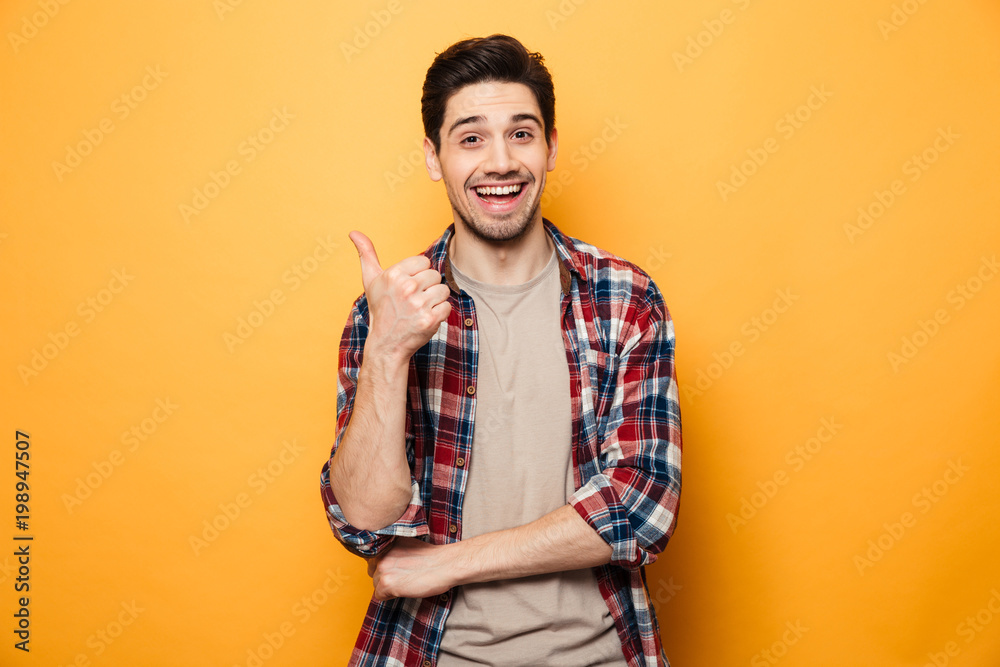 Fototapeta Portrait of a smiling young man pointing finger away