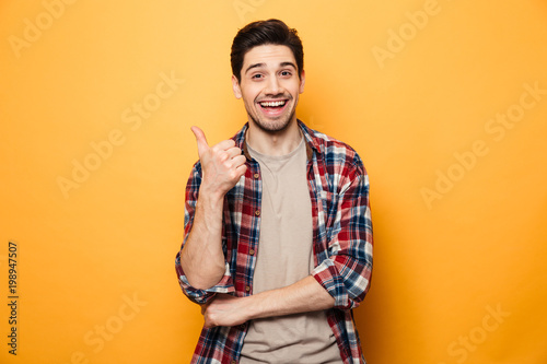 Portrait of a smiling young man pointing finger away