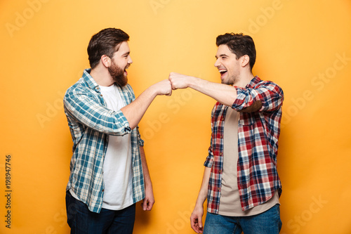 Valokuva  Portrait of a two happy young men giving fist bump