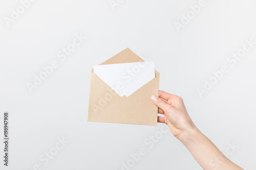 Fotografia  partial view of woman holding kraft envelope with blank card in hand isolated on
