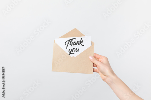 Fotografía  partial view of woman holding kraft envelope with thank you card isolated on whi