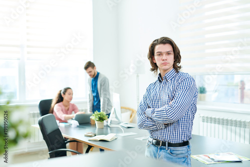 Fototapety, obrazy: Serious successful handsome young male manager in eyeglasses crossing arms on chest and looking at camera while his colleagues discussing presentation on laptop