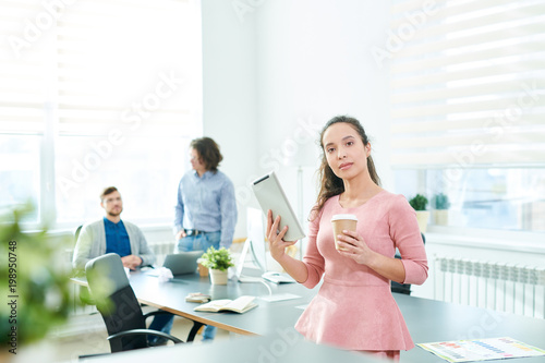 Fototapety, obrazy: Serious confident beautiful young Hispanic female manager with modern device and coffee cup looking at camera while her colleagues discussing business plan in background