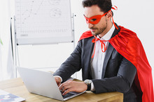 Super Businessman In Mask And Cape Working With Laptop In Office
