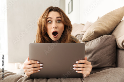 Fototapeta Image of excited european woman lying on sofa in living room, and expressing int