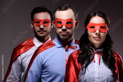 Photo  super businesspeople in masks and capes looking at camera isolated on grey