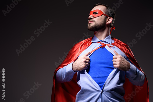 Fotografie, Obraz  handsome super businessman in mask and cape showing blue shirt and looking away