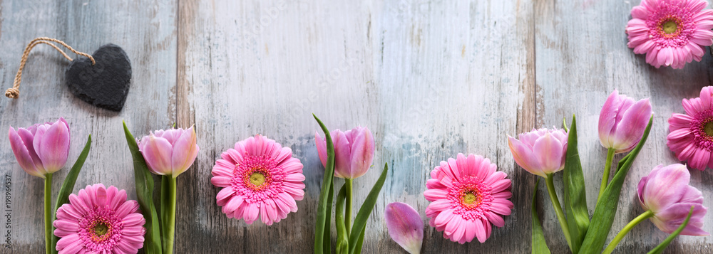 Fototapeta Spring flowers with a heart on shabby wood