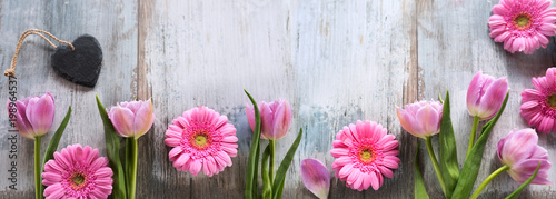 Spring flowers with a heart on shabby wood