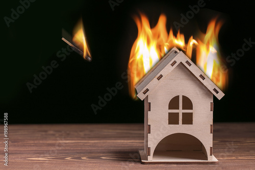 Photo House fire concept. Toy house with flames and match with fire