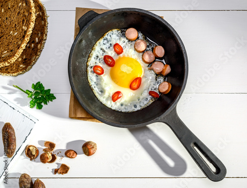 Foto op Canvas Gebakken Eieren fried chicken egg with pieces of sausage in a black cast-iron frying pan