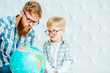 Happy beard dad and son sitting on the floor and looking at globe together at home with white polygonal background.