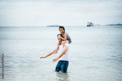 Father and daughter having fun on beach Poster