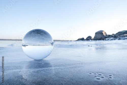 Glass orb on a frozen lake in the winter