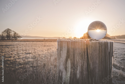 Winter sunrise with sun in a glass orb
